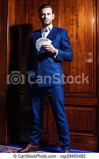 Un hombre guapo con traje posa con tarjetas en el fondo de madera - csp29405482