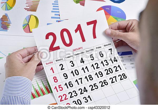 Un joven hombre de negocios con un calendario de 2017 - csp43320012