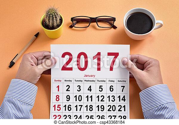 Un joven hombre de negocios con un calendario de 2017 - csp43368184