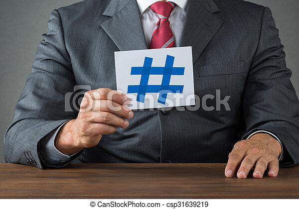 Hombre de negocios mostrando hachís en el escritorio - csp31639219