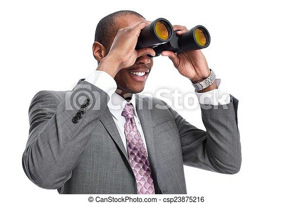 Un hombre de negocios afroamericano con prismáticos. - csp23875216