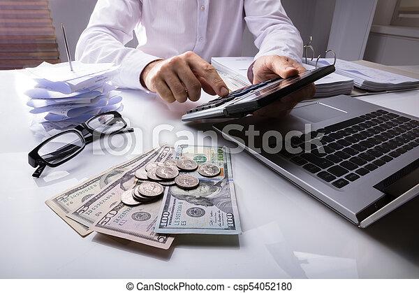 Empresario usando calculadora con dólar - csp54052180