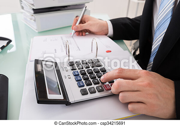 Empresario calculando la factura con calculadora - csp34215691