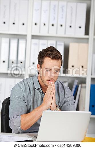Un hombre de negocios serio usando portátil en la oficina - csp14389300