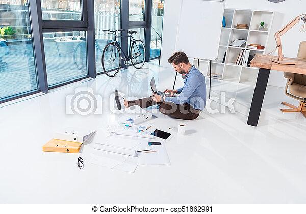 Hombre de negocios usando portátil en la oficina - csp51862991