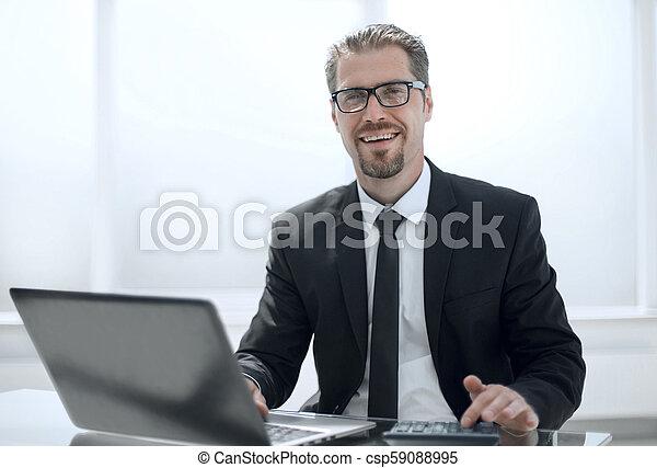 Hombre de negocios en la oficina trabajando en portátil - csp59088995
