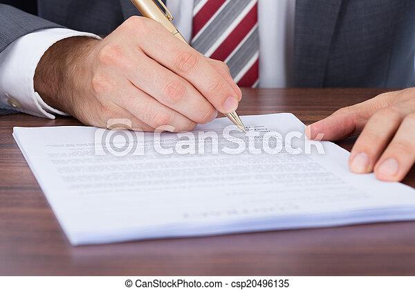 Empresario firmando documentos en el escritorio - csp20496135