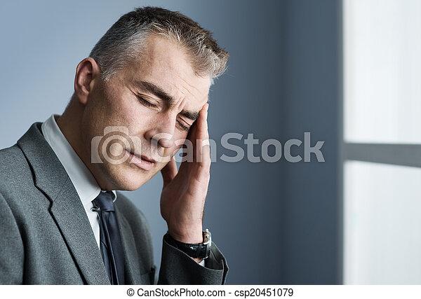 Un hombre de negocios estresado con dolor de cabeza - csp20451079