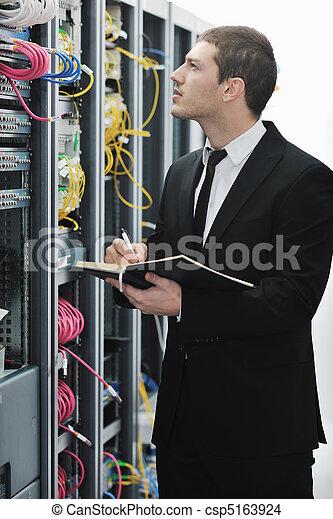 Empresario sin libreta en la sala de servidores de la red - csp5163924