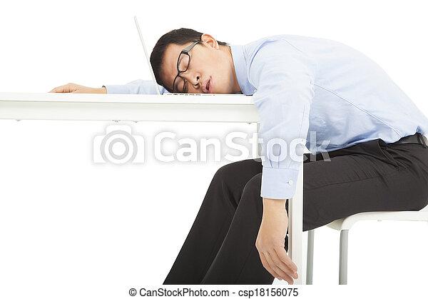 Un hombre de negocios cansado duerme en el escritorio - csp18156075