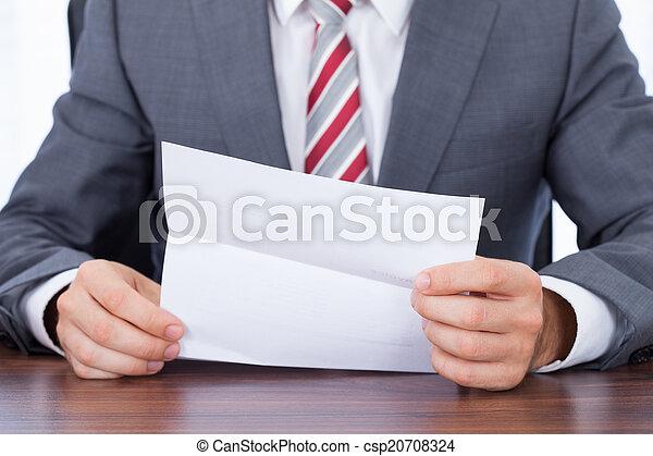 Un hombre de negocios leyendo documentos en el escritorio - csp20708324