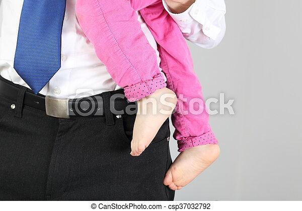 Hombre de negocios en traje con un niño en el brazo - csp37032792