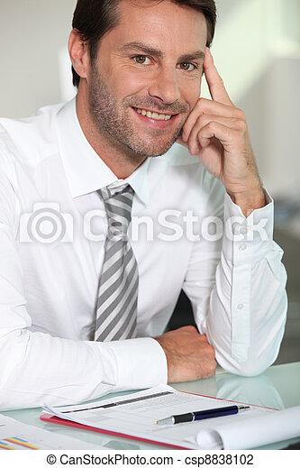 El hombre de negocios se sentó en el escritorio - csp8838102