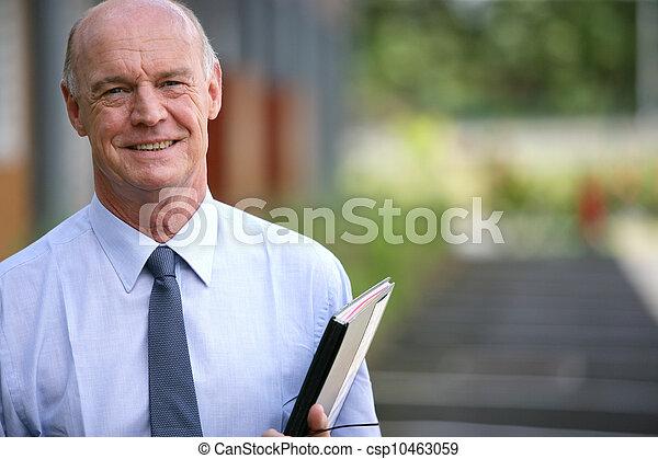 Un empresario sonriente sosteniendo una carpeta - csp10463059