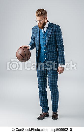 Hombre guapo de traje con pelota de baloncesto - csp50990210