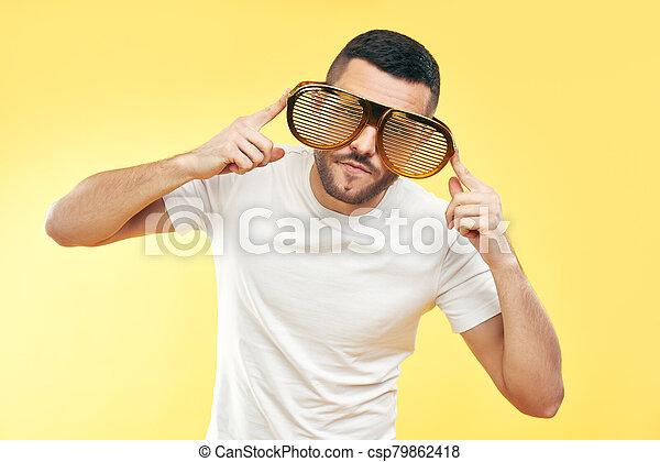 hombre, joven, gafas chistosas, encima, fondo amarillo, fiesta - csp79862418