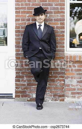 Hombre de traje y corbata apoyado contra la pared - csp2673744