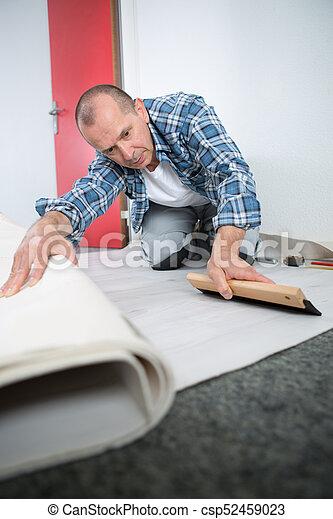 Hombre poniendo alfombra - csp52459023