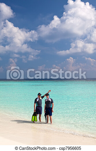 Dos hombres en el mar con el equipo para bucear - csp7956605