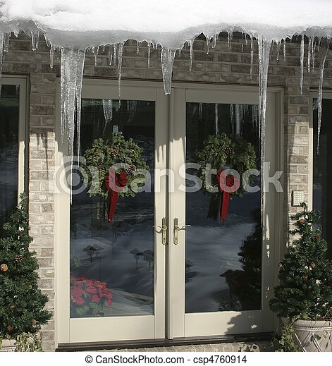 Double Glass Doors As Entry To A Home With Wreath Decorations, Icicles  Hanging From The Eaves, All Bathed In Bright Sunlight
