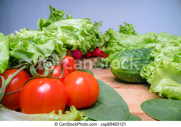 Home grown and harvested vegetables on wooden table background. Fresh lettuce, salad, tomato, radish, spinach and cucumber. Healthy eating lifestyle - csp68463121