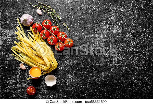Home made raw pasta with egg, tomatoes and thyme. - csp68531699