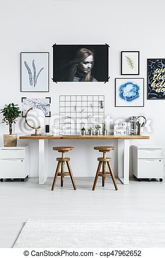 Trendy home office with modern furniture and posters