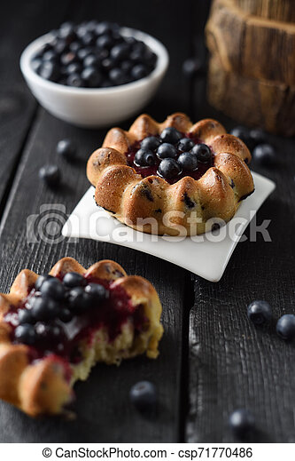Homemade blueberry cakes with raw forest blueberries on black background. Low key still life with natural lighting - csp71770486