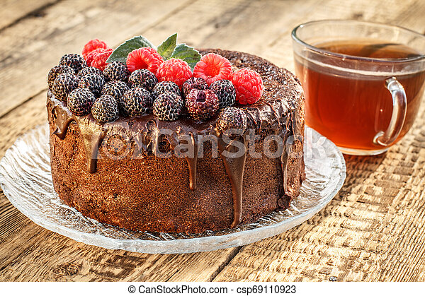 Homemade chocolate cake decorated with black and red raspberries on glass plate with cup of tea. - csp69110923