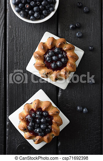 Homemade dessert. Yummy cakes with jam and wild bilberries on black background top view copy space. Low key still life with natural lighting - csp71692398