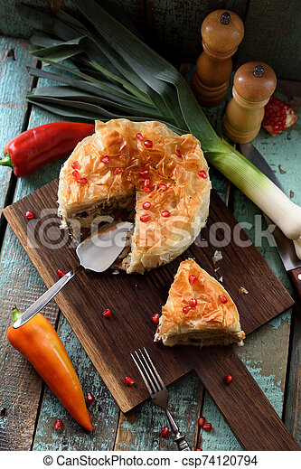 Homemade filo dough pie with raw vegetables and pomegranate seeds on oak board on blue wooden background. Low key still life with natural lighting - csp74120794