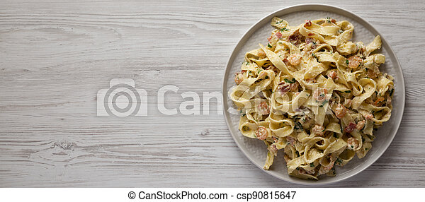 Homemade Garlic Shrimp Bacon Alfredo on a plate on a white wooden background, top view. Flat lay, overhead, from above. Space for text. - csp90815647
