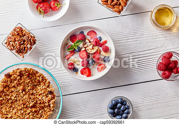 Homemade granola in a plate, sliced banana, berries, almonds, walnuts and white bowl with natural organic breakfast on white wooden table. - csp59392661