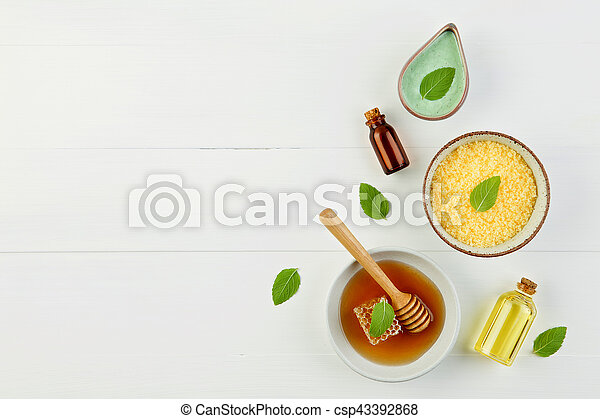 Homemade lemon essential oil, salt bath and fresh honey in the plate with honeycomb, dipper and mints on rustic background from top view. Flat lay good for background and space. - csp43392868