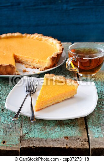 Homemade open yummy pumpkin pie with black tea on old wooden background - csp37273118