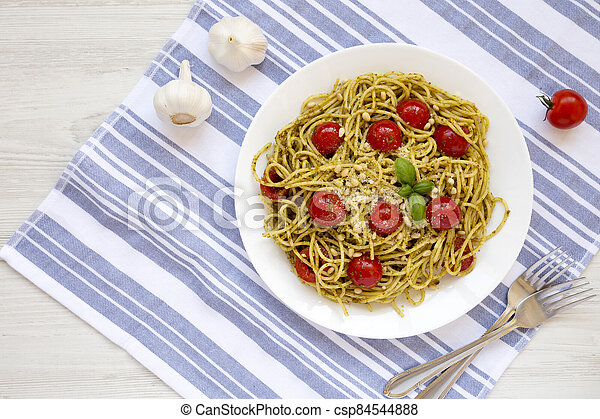 Homemade Pesto Pasta with Tomatoes and Pine Nuts on a white plate, overhead view. Flat lay, top view, from above. Space for text. - csp84544888