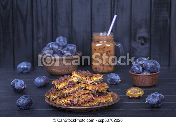 Homemade plum pie in plate, plum smoothies and raw plums on black wooden background - csp50702028