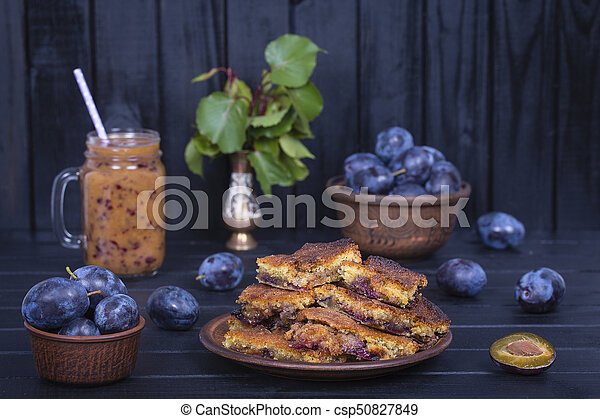 Homemade plum pie in plate, plum smoothies and raw plums on black wooden background - csp50827849