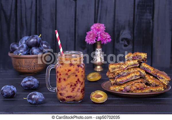 Homemade plum pie in plate, plum smoothies and raw plums on black wooden background - csp50702035