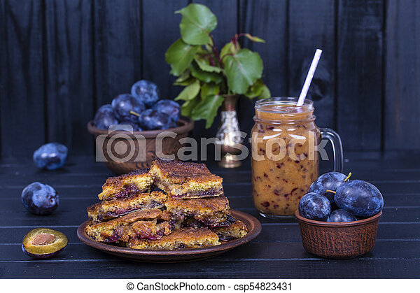 Homemade plum pie in plate, plum smoothies and raw blue plums on black wooden background, - csp54823431