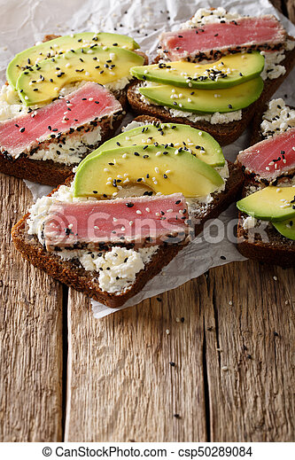 Homemade sandwiches with tuna steak in sesame, avocado and cream cheese close-up. vertical - csp50289084