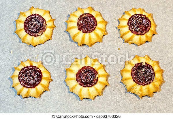 Homemade shortbread cookies with jam on cooking paper. Background - csp63768326