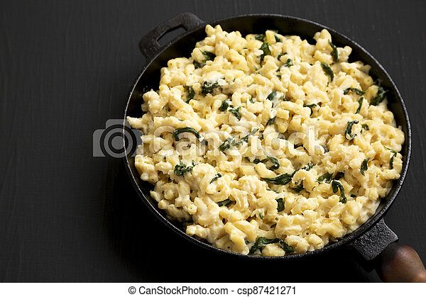 Homemade Spinach Mac and Cheese in a cast-iron pan on a black background, side view. Space for text. - csp87421271