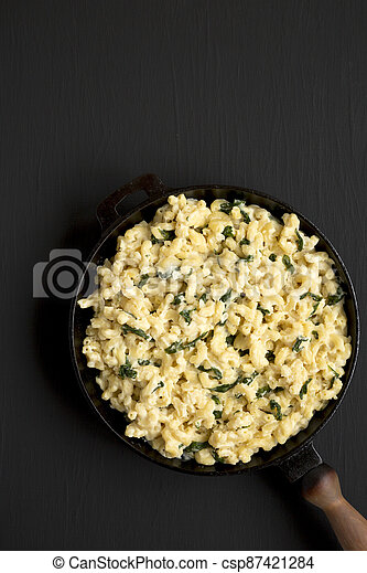 Homemade Spinach Mac and Cheese in a cast-iron pan on a black background, top view. Flat lay, overhead, from above. Copy space. - csp87421284