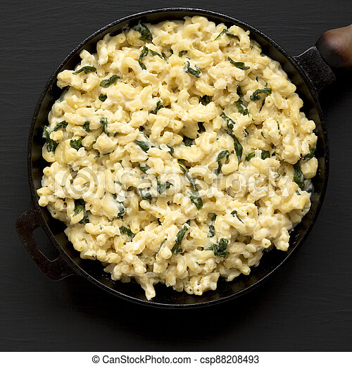 Homemade Spinach Mac and Cheese in a cast-iron pan on a black background, top view. Flat lay, overhead, from above. Copy space. - csp88208493