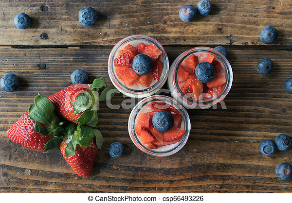 Homemade strawberry yogurt with jam and pieces of fruit on a wooden board - csp66493226