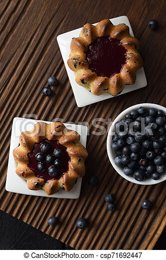Homemade sweets. Yummy cakes with jam and wild bilberries on ribbed oak cutting board top view copy space. Low key still life with natural lighting - csp71692447