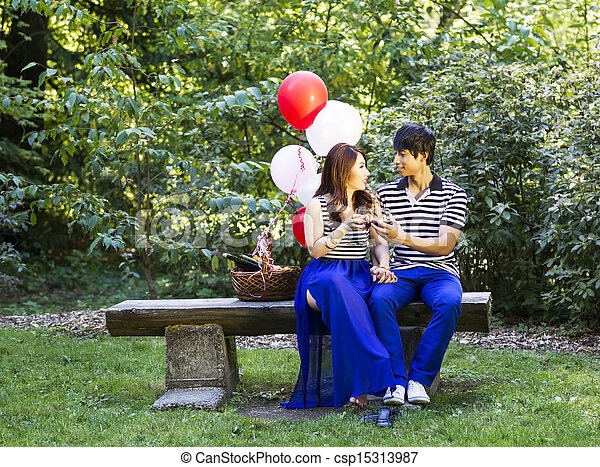 Horizontal photo of young adult couple sitting on log bench with glasses filled with red wine being held in their hands with balloons, green grass and trees in background  - csp15313987
