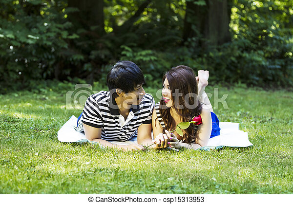Horizontal photo of young adult couple, lying on blanket, while looking at each other with green grass and trees in background   - csp15313953