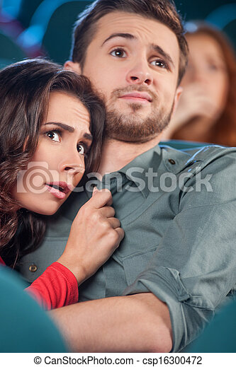 Horror movie. Terrified young couple hugging while watching movie the cinema - csp16300472